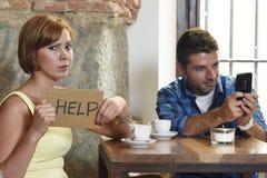 在咖啡店手机上瘾者的夫妇供以人员忽略沮丧的妇女请求帮忙 库存照片