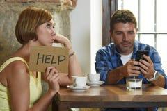在咖啡店手机上瘾者的夫妇供以人员忽略沮丧的妇女请求帮忙 库存图片
