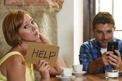 在咖啡店手机上瘾者的夫妇供以人员忽略沮丧的妇女请求帮忙 免版税库存照片