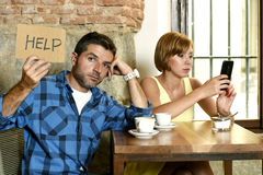 在咖啡店手机的夫妇使忽略沮丧的人的妇女上瘾请求帮忙 库存图片