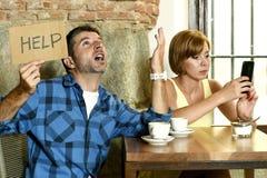 在咖啡店手机的夫妇使忽略沮丧的人的妇女上瘾请求帮忙 免版税库存图片