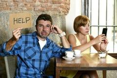 在咖啡店手机的夫妇使忽略沮丧的人的妇女上瘾请求帮忙 免版税库存照片