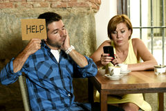 在咖啡店手机的夫妇使忽略沮丧的人的妇女上瘾请求帮忙 库存照片