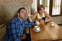 在咖啡店手机的年轻夫妇使忽略沮丧的人的妇女上瘾 免版税库存图片
