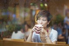 在咖啡店的中国妇女饮用的咖啡 库存照片
