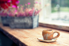 在咖啡店的咖啡杯与在背景的花盆 被过滤的图象:十字架被处理的葡萄酒作用 库存图片