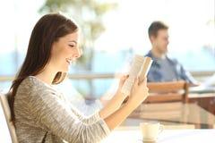 读在咖啡店的妇女一本书 库存图片