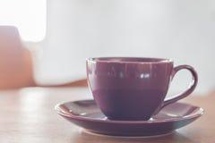 在咖啡店的紫罗兰色咖啡杯 库存照片