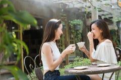 在咖啡店谈话的两名妇女集会没有用途智能手机 库存图片