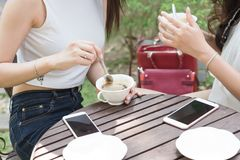 在咖啡店takl的两名妇女集会没有用途智能手机 免版税图库摄影