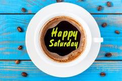 在咖啡杯写的愉快的星期六在蓝色木背景用豆 免版税库存图片