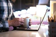 在咖啡杯或茶杯子附近供以人员握手在家庭办公室 免版税库存照片