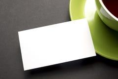 在咖啡杯的名片空白在办公室桌上 公司文具烙记的大模型 免版税图库摄影