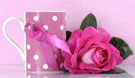 在咖啡杯的桃红色丝带慈善标志与上升了 图库摄影