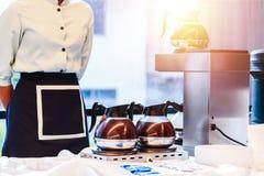 在咖啡杯附近的女服务员立场在煤气炉和咖啡机器 免版税库存照片