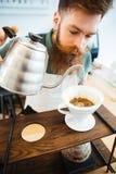 在咖啡渣的Barista倾吐的水与过滤器 免版税库存图片