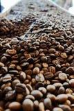 在咖啡烘烤器的新近地烤咖啡豆 库存照片