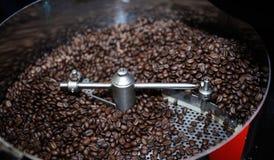 在咖啡烘烤器的烤咖啡豆 图库摄影