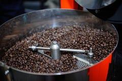 在咖啡烘烤器的烤咖啡豆 免版税库存照片