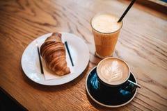 在咖啡热奶咖啡和橙汁旁边的法国传统新月形面包点心在一个咖啡馆早餐 免版税库存照片