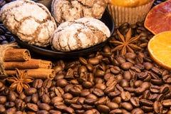 在咖啡疏散豆有一块板材用巧克力曲奇饼在桂香蛋糕、绿色枝杈和切片旁边棍子  库存图片