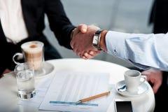 在咖啡的企业握手 免版税库存照片
