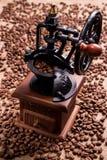 在咖啡粒背景的减速火箭的磨咖啡器  图库摄影
