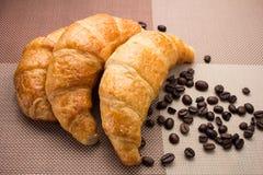 在咖啡豆上把放的新月形面包 库存图片