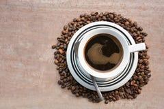 在咖啡豆中间的黑暗的咖啡 免版税库存照片