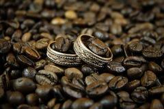在咖啡豆的两个金子婚戒 免版税图库摄影