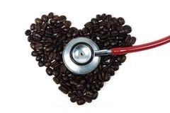在咖啡豆的听诊器在心脏形状  免版税库存照片