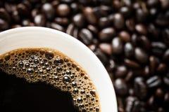 在咖啡豆的咖啡杯 图库摄影