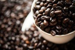 在咖啡豆的白色杯子 免版税库存照片