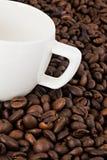 在咖啡豆背景的加奶咖啡杯子  图库摄影