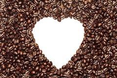 在咖啡豆背景的白色心脏形状 免版税库存照片