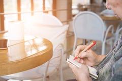 在咖啡馆咖啡店resta的老年长资深妇女文字笔记 库存照片