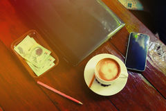 在咖啡馆商店咖啡杯和手机的膝上型计算机在桌上 库存照片