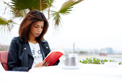 在咖啡馆坐江边和读书的逗人喜爱的女孩 免版税库存图片