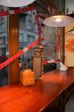 在咖啡馆的一盏灯点燃的桌上的磨咖啡器在windo附近 免版税库存照片
