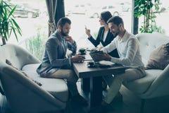在咖啡馆的企业交涉 三个伙伴谈论Th 库存照片