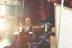 在咖啡馆的休息期间妇女在有朋友的互联网聊天通过手机 免版税库存照片