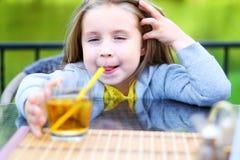 在咖啡馆的可爱的小女孩饮用的苹果汁 免版税库存图片