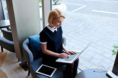 在咖啡馆的咖啡休息期间女实业家通过便携式的网书检查电子邮件在互联网 免版税库存图片