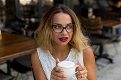 在咖啡馆的女商人饮用的早晨热奶咖啡 库存图片