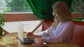 在咖啡馆的女实业家佩带的玻璃工作和谈话由视频通信 股票录像