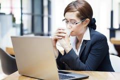 在咖啡馆的女实业家饮用的咖啡 库存照片