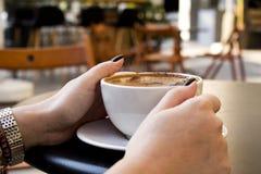 在咖啡馆的妇女手饮用的咖啡 免版税库存图片