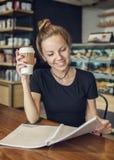 在咖啡馆的妇女读书与一杯咖啡 免版税图库摄影