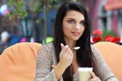在咖啡馆的妇女饮用的茶户外 免版税库存照片