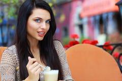 在咖啡馆的妇女饮用的茶户外 免版税库存图片